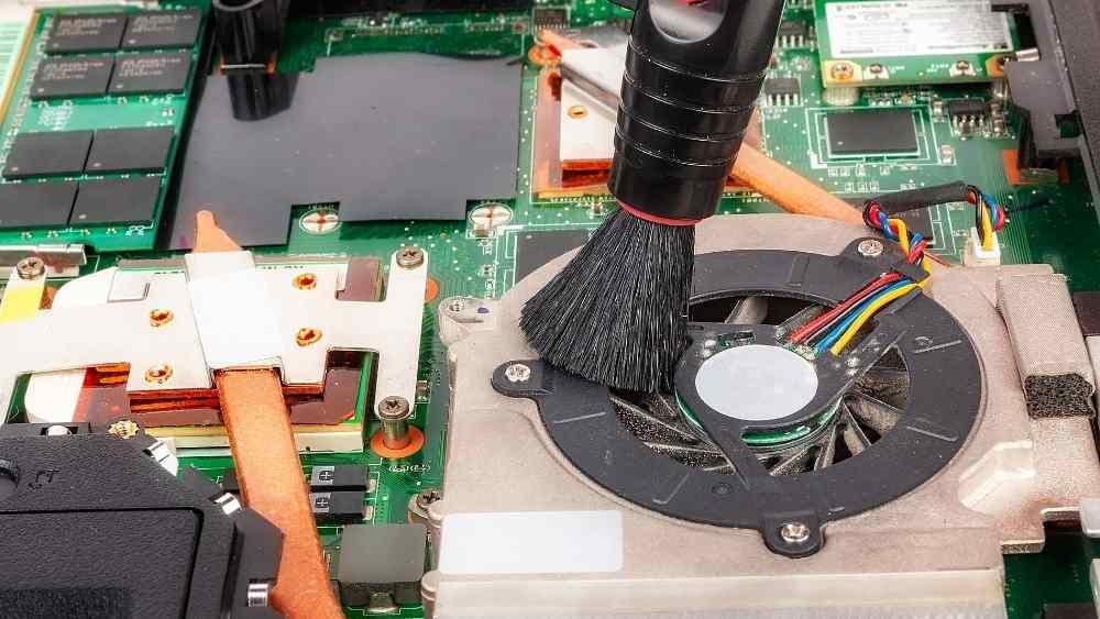 a technician cleaning dust out of laptop fan
