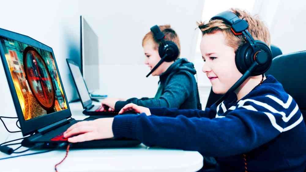two kids playing games on their laptop